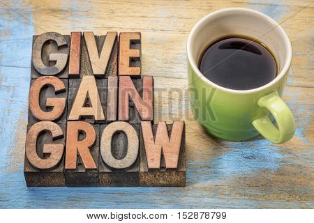 give, gain and grow word abstract  -personal development or motivational concept - text  in vintage letterpress wood type printing blocks with a cup of coffee