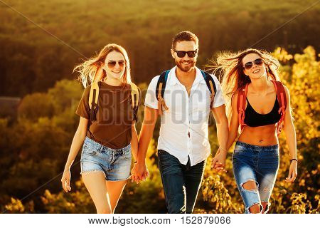 Bearded handsome man and two pretty sexy cute girls or women in jeans and shorts with backpacks outdoor on sunny day walking on forest background