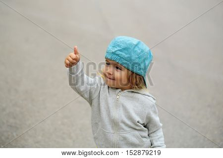 Cute baby boy child with curly blond curly hair in hoody and blue hat show cool outdoor on gray background