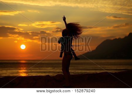 Mother young woman and son baby boy silhouettes plays on beach near sea or ocean water in evening or twilight sunset summer day on natural background