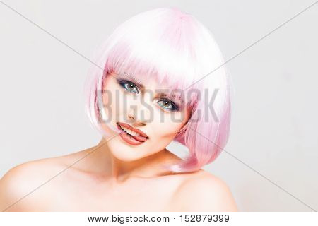 sexy glamour girl or woman with fashionable makeup on pretty face and short hairstyle or pink wig in studio isolated on white background