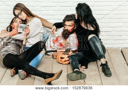 Zombie people of bearded man with beard and three girls young bloody women with pumpkin and axe ready for halloween on wooden floor