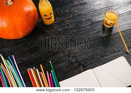 Big pumpkin, juice, paper and color pencils on the table for making Halloween party decorations