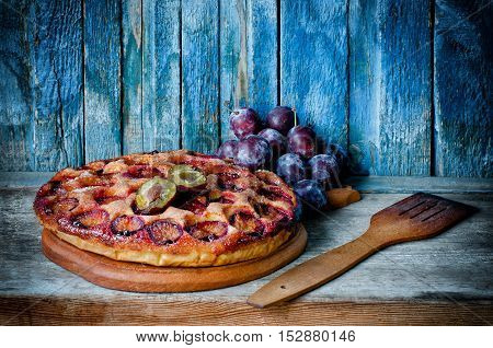 Plum cake on a wooden table fresh plum on the blue background