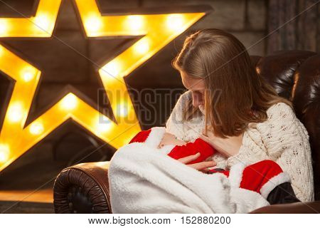 Newborn baby wearing as Santa Claus breast feeding. Selective focus on the kid s face. Homemade Christmas.