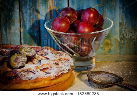 Pialat with plums plum cake with powdered sugar a metal strainer