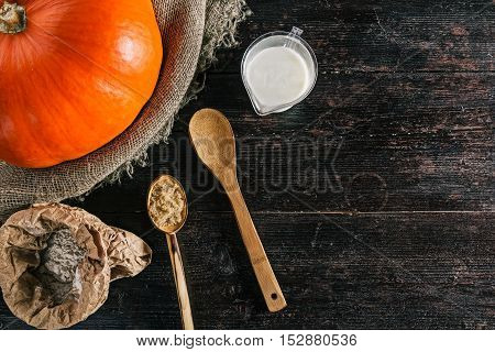 Ingredients for dough making and pumpkin on the kitchen desk