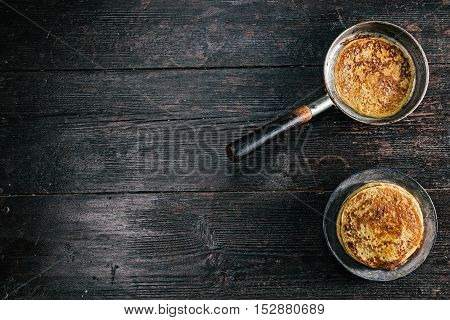 Stack of prepared pancakes and frying pan on the kitchen desk