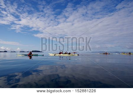 Kayakers enjoy a morning paddle in calm seas of the outer islands along the central coast of British Columbia. The high clouds and blue sky are reflected in the glassy sea.