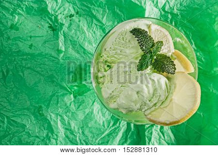 Green icecream with fresh lemon and mint served in glass bowl over green wrinkled background