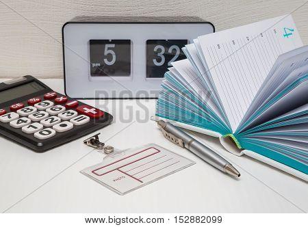 office supplies notebook with pen badge watch still life