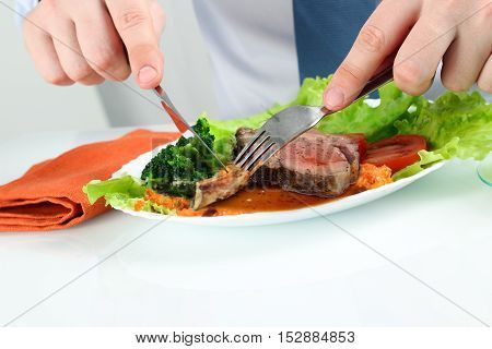 Young business man eating a healthy salad with steak
