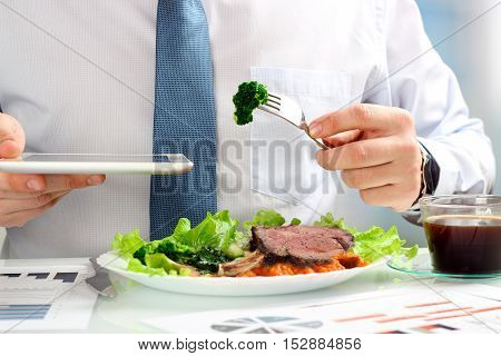 Close-up of businessman working on marketing strategy during business lunch eating juicy club steak