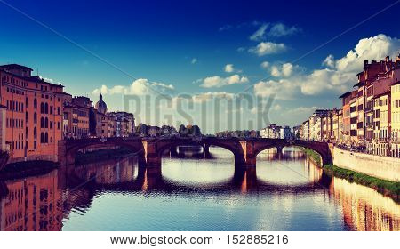 View from the river to the famous italian medieval bridge - Ponte Vecchio in Florence with blue sky and clouds, travel outdoor Italy sightseeing background