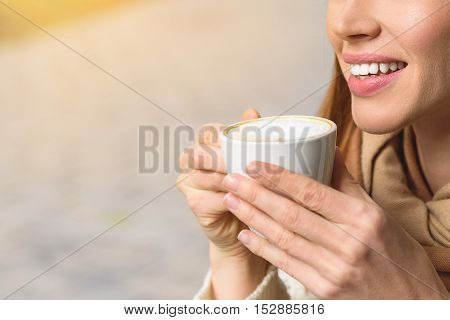 Close up of happy girl warming up with hot coffee outdoors. She is holding cup and smiling. Copy space in left side