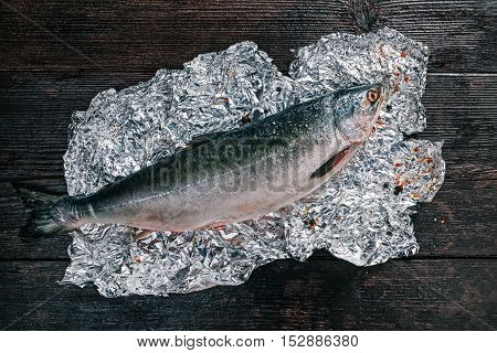 Fresh whole salmon fish on foil sheet with spices. Flat lay