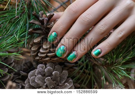 Female hand with green foil nail design and fir cones on background.