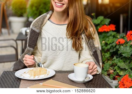 Happy young woman is enjoying breakfast in cafeteria. She is eating pastry and drinking coffee. Lady is sitting covered by blanket and smiling