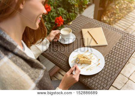 Pretty girl is eating sweet cake in cafe outdoors. She is holding cup of coffee and smiling. Lady is sitting and warming up by blanket