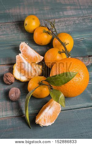Tangerines with branch, leafs, orange slices and wallnuts on green wooden table.