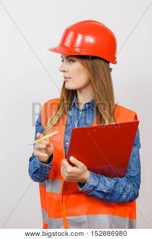 Woman construction worker builder structural engineerin in orange vest red hard helmet holds pen file pad. Safety in industrial work. Studio shot