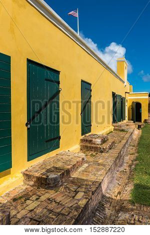 Interior courtyard of Fort Christiansted in St. Croix Virgin Islands. Green stable doors against yellow walls