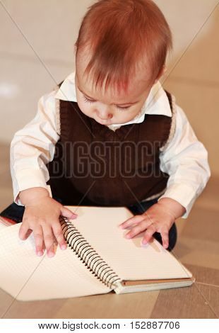 little boy studies a notebook, learns surrounding objects