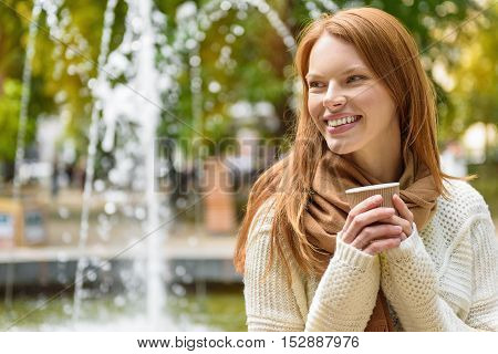 Cheerful young woman is warming up by hot beverage in park. She is standing near fountain and smiling