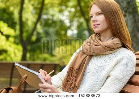 Pensive young girl is enjoying nature and drawing. She is sitting on bench with relaxation