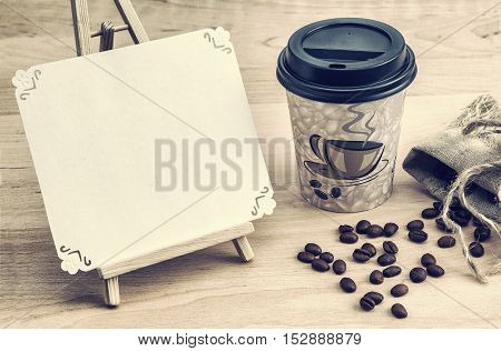 coffee beans and a cup on a wooden surface disposable tableware title retro style