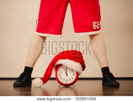 Closeup of man legs and alarm clock with santa claus hat. Christmas time season concept. Instagram filter.