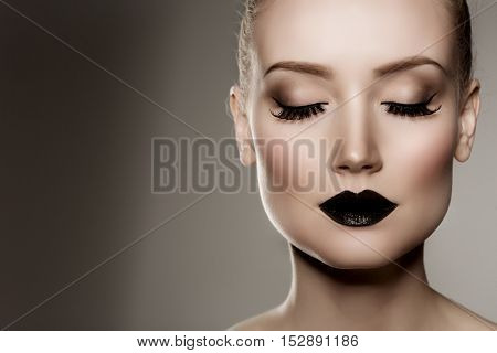 Black lips. Halloween Makeup. Luxury beautiful woman with dark lipstick. Beauty stylish girl with closed eyes