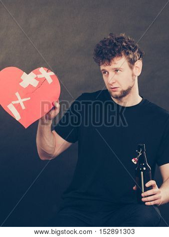 Addiction and trouble of drinking. Young man with bottle of alcohol on dark background. Broken heart and sadness concept.