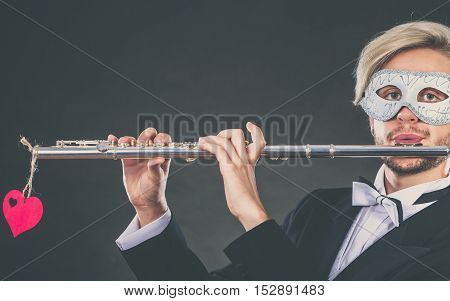 Man In Carnival Mask Playing Flute