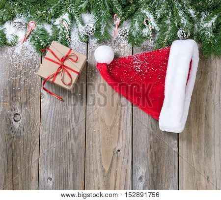 Christmas holiday wooden background with fir branches snow Santa cap and gift box forming upper border