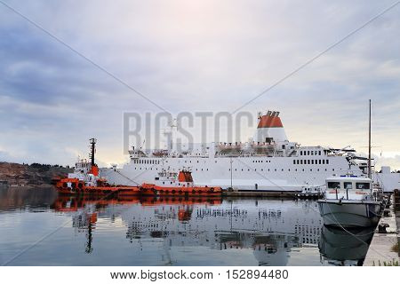 White Ferryboat And Red Tugboats In Port
