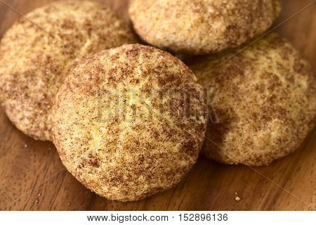 Homemade snickerdoodle cookies with cinnamon and sugar coating on wooden plate photographed with natural light (Selective Focus Focus in the middle of the cookie in the front)