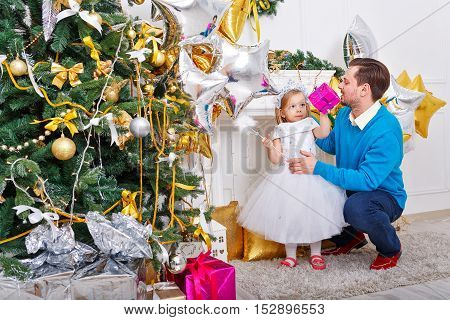Father and daughter near a Christmas tree. Father hugging daughter and little cute girl holding a gift and magic wand. The festive mood. Family celebration.
