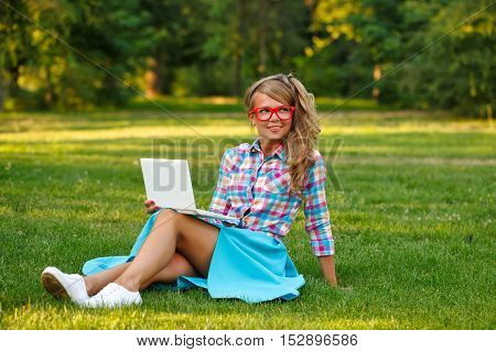 Lovely attractive girl with a laptop. She smiles and sits on a green lawn in the park. A student takes a break from lessons.
