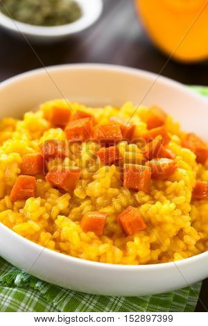 Pumpkin risotto prepared with pumpkin puree roasted pumpkin pieces on top photographed with natural light (Selective Focus Focus one third into the risotto)