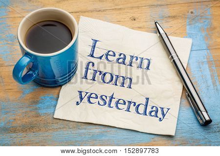 Learn from yesterday - handwriting on a napkin with a cup of espresso coffee