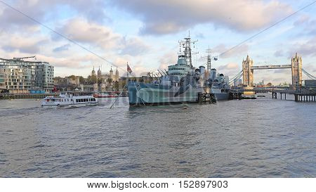 LONDON UNITED KINGDOM - NOVEMBER 23: HMS Belfast and Tower Bridge in London on NOVEMBER 23 2013. Royal Navy Floating War Museum at Thames RIver in London United Kingdom.