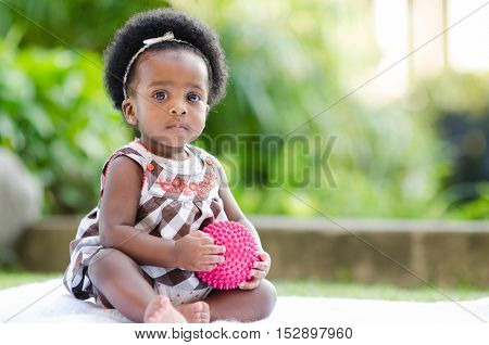 Portrait of an African American baby girl sitting outdoors playing with a ball