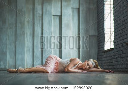 Dancing is silent poetry. Young contemporary dancer with blond hair lying on wooden floor in dancing studio
