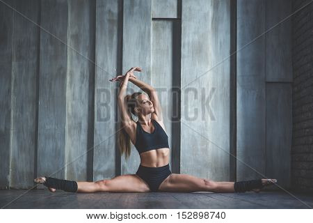 Practice makes perfect. Pretty sporty strong slim and fit young woman sitting, doing split and stretching exercises