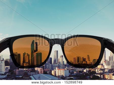 Sun glasses with light brown lens looking to city view