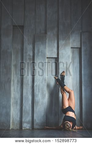 Perfect poise. Beautiful young female classical ballet dancer wearing black clothes in class dance against grey wall
