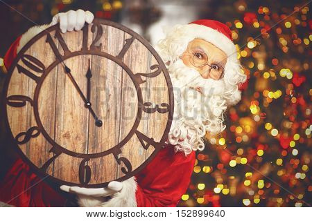 Christmas concept Santa Claus and a large clock