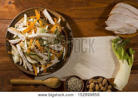Salad with turkey fennel and almonds in a clay plate on a wooden background