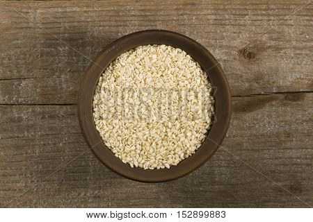 Sesame seeds in a clay bowl on the old wooden background